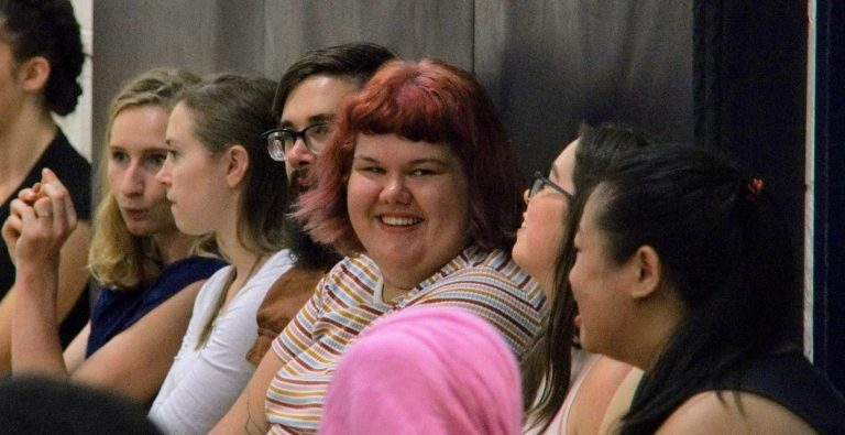 Image of Author Jessie Goyette sitting with several othe rpeople smiling at the camera