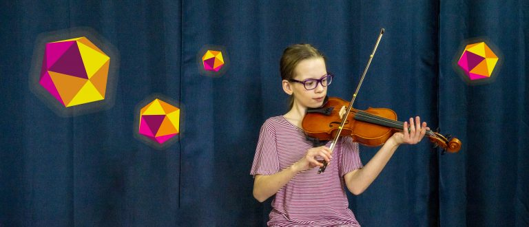 Darcy, a young person, sitting an dplaying violin infront of dark curtain, with colourful dodecahedrons floating around them